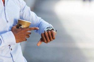 Mann mit Kaffee schaut auf die Uhr